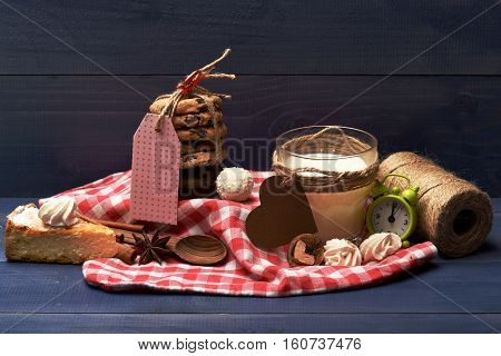 set of cup with juice or milk alarm clock apple pie spoon cinnamon anise cookies with pink label twine hank coconut candy and marshmallow on checkered pink napkin on vintage wooden background
