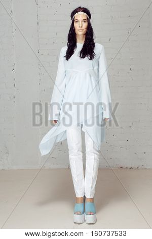 Woman modern hippies, is exactly in the center of the studio at her the wind blows. Nice model in studio with white clothes staying near grey bricks wall