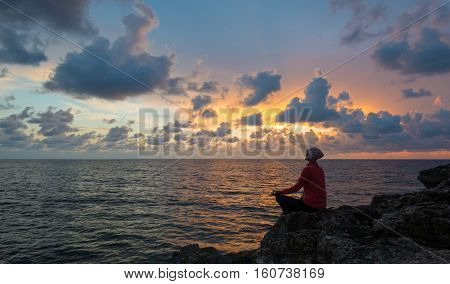 Woman sits as yogi on rock. Beautiful sunset over sea in background.