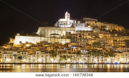 Skyline of Ibiza Dalt Vila downtown closeup at night with light reflections in the water