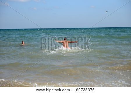 Young Man In The Summer Vacation, Enjoying The Sea Waves Under The Scorching Sun. Holiday