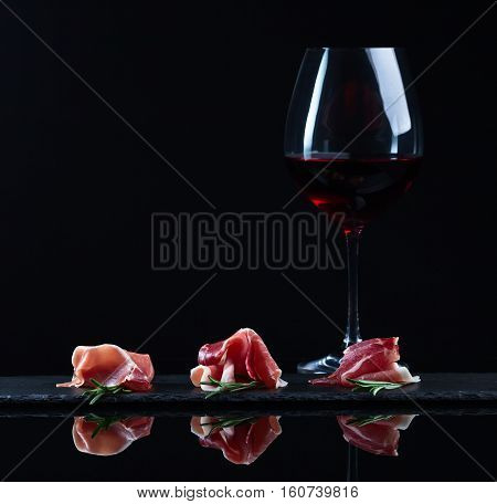 Jamon With Rosemary And Glass Of Red Wine On A Black Background
