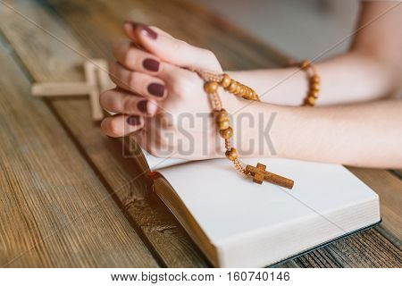 Womans Hands With Wooden Rosary And Holy Bible
