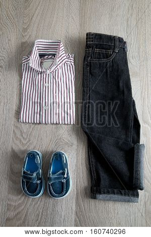 Boy Outfit. Striped Shirt, Denim Pants And Blue Shoes On Grey Wooden Background.. Top View.