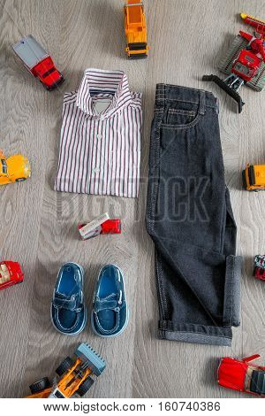 Boy Outfit Near Car Toy. Striped Shirt, Denim Pants And Blue Shoes  Yellow  Red Cars. Top View.