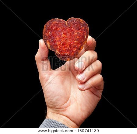 Man hand is holding a heart shape slice of croatian kulen on a black backround.