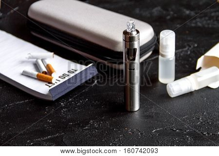 elimination of tobacco smoking electronic cigarette on dark background close up