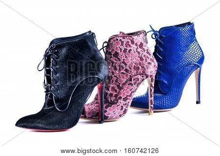 Ukraine Kiev - August 25 2016: Sexy women's shoes on a white background. Bright blue burgundy lace and black fur ankle boots. Footwear of three different colors and materials - illustrative editorial