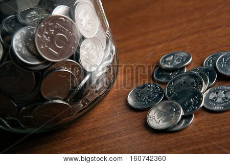 bank with coins and a bunch of Russian rubles coins on a wooden surface close up