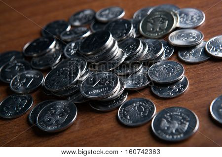 bunch of Russian rubles coins on a wooden surface close up