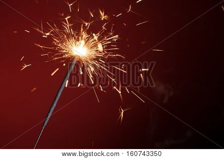 Christmas sparkler on red background