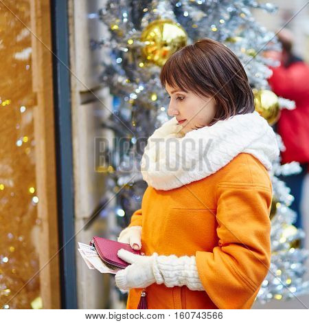 Worried Young Woman Holding Money
