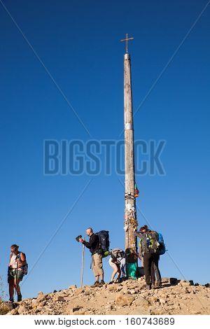 FONCEBADON SPAIN - AUGUST 05: Pilgrims next to the iron cross called cruz de Hierro along the way of St. James on August 05 2016