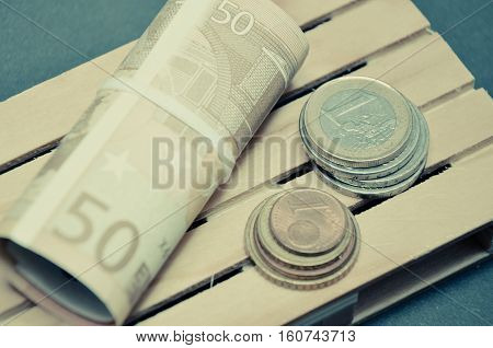 Retro vintage photo effect of Euro banknotes and coin money on the pallet. macro photo european currency.