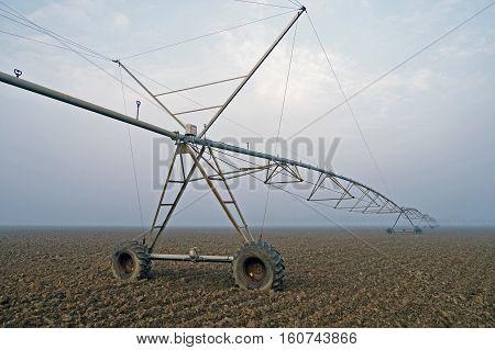 Crop Irrigation using the center pivot sprinkler system on the winter fog