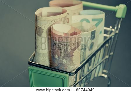 Retro vintage photo effect of Euro banknotes in the shopping cart. Easy access on loan. Macro photo of european currency.