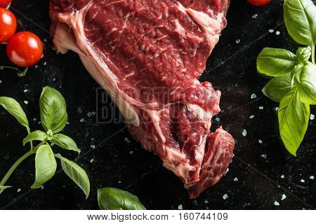Fresh Steak Served With Spices, Tomatoes And Leafs Of Basil On Marble Background. Uncooked Beefsteak