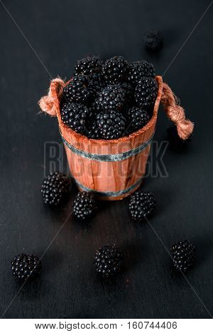 Black Raspberries In A Wooden Basket And On   Table. Close Up.