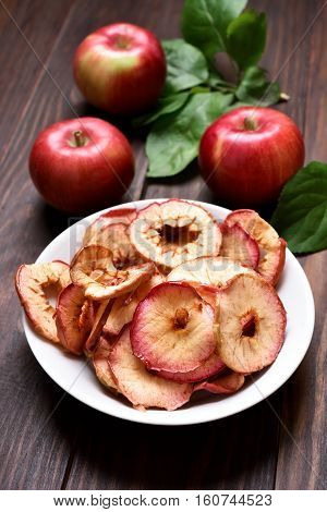 Apple chips and fresh fruits on wooden table