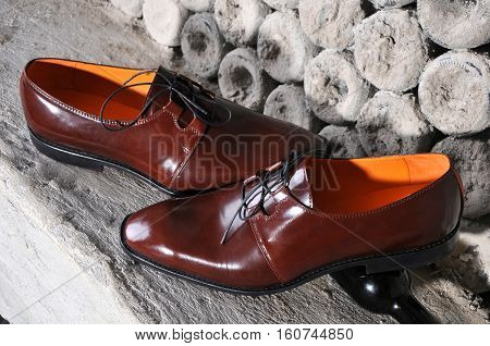 Classic shiny brown mens shoes standing on interesting background stylized bottles