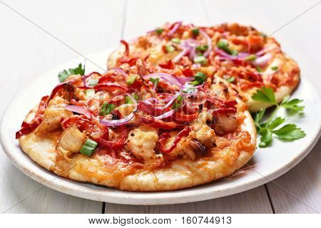 Pie pizza with chicken meat and red bell pepper on white wooden background