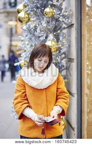 Worried Young Woman Holding Purse In Shopping Mall