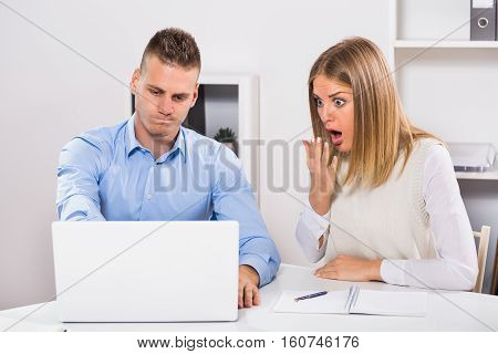 Worried businessman and businesswoman in panic are using laptop and working at their office.