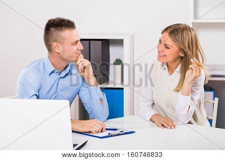 Young woman is flirting with her colleague at work.