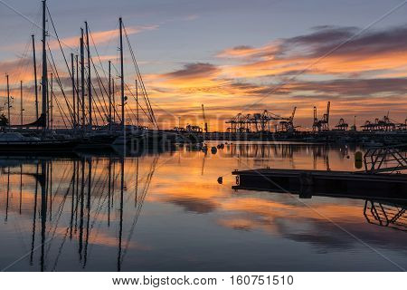 Twilight at harbor sunrises silhouettes of docked sailboats and cargo port cranes red orange colors in the sky and water reflection horizon