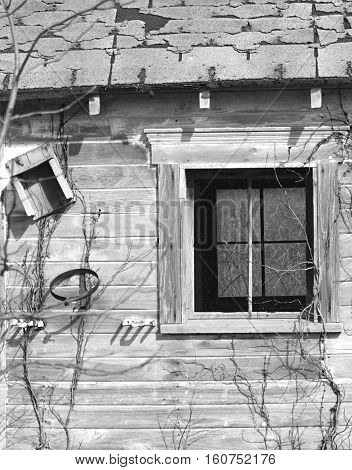 Close-up black & white image of old wood shed with line of sight through window.