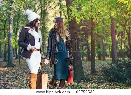 Two elegant young woman walking through a park in autumn chatting and laughing as they walk through woodland close up with copy space
