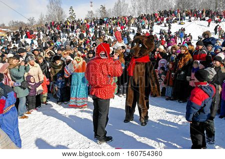 Gatchina, Leningrad region, Russia - March 5, 2011: Maslenitsa. a traditional spring holiday at the Russian peoples. Lead as clown holds competitions with a bear.