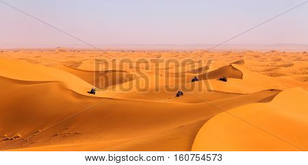 Tourists Driving Quads And All-terrain Vehicles In Sahara Dunes
