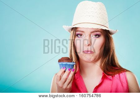 Diet dilemma grow fat from eating sweets concept. Sad unhappy woman holds cake cupcake in hand blue background