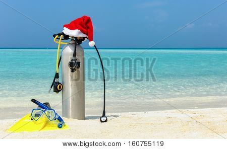 Scuba diving gear on tropical beach with a christmas hat