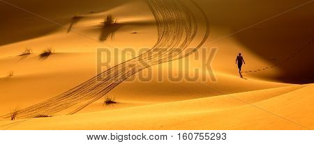 Merzouga Morocco - Feb 24 2016: Woman trekking along hot desert beautiful orange sandy dunes exploring Sahara active vacation discovering nature concept