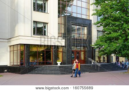 MINSK BELARUS - OCTOBER 1 2016: Unidentified people go on street near building of Law Faculty of Belorussian State University Minsk Belarus