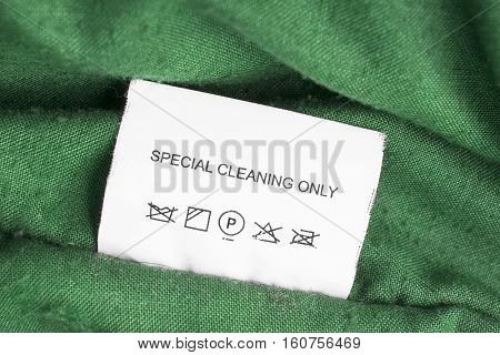 Washing instructions label on green cloth closeup