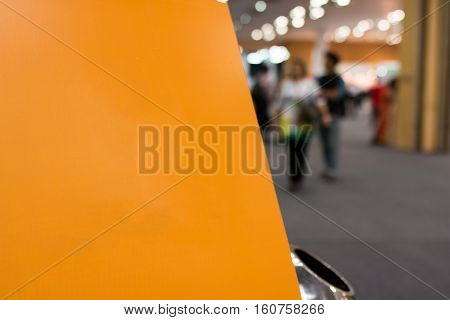 Blank Orange Banner Board For Text And Trashcan With Blur Image Of People In Exhibition Or Shopping