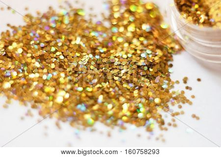 Gold sequins. placer gold glitter texture and background Gold glitters on a light background Glowing New Year or Christmas background. Bright lights and glitter powder. shallow depth of field