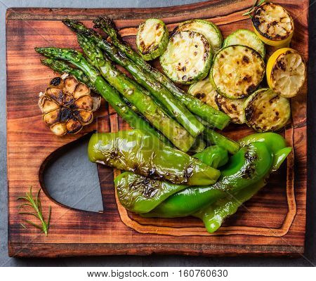 Grilled green vegetables - zucchini, asparagus, bell pepper, garlic and lemon on wooden cutting board. Top view