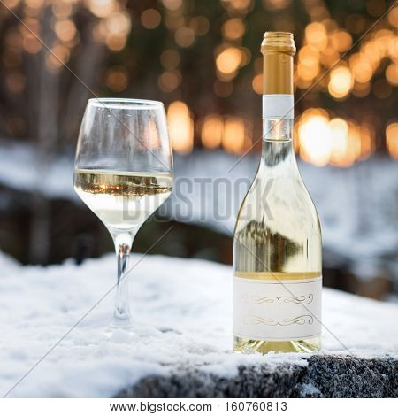 Love, romance, holiday, New Year celebration concept. Bottle and glass of white wine chilled by snow in winter forest on sunset