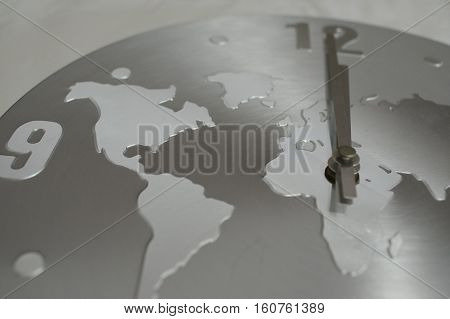 Silver clock with background of the world