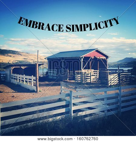Inspirational quote on scenic farm landscape scene with red barn stable behind white fences,lake and hills in background. Embrace simplicity.  Scenic landscape with inspirational text.