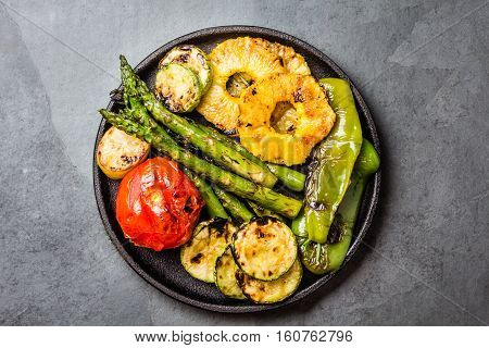 Grilled vegetables - tomatoes, asparagus, zucchini, bell pepper, pineapple slices and fresh cheese on cast iron black plate, gray slate background. top view