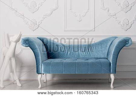 luxurious blue velvet sofa and and white sculpture of a dog near the armrest behind a white wall