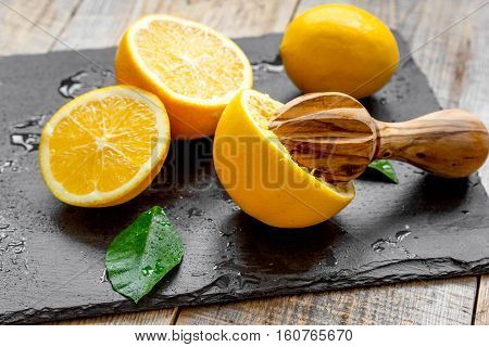 cut oranges in half and juicer on wooden background wooden background close up