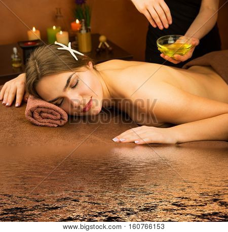 Beautiful woman in spa salon having spa therapy aroma oil procedure with hands of masseur with water reflection