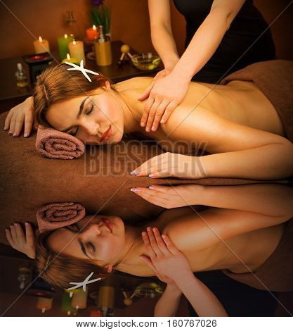 Beautiful lying woman in spa salon having massage with water reflection