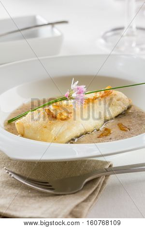 A fried hake fillet served a garlic sauce and garnished with fried garlic slices.